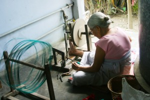Abok carefully and skilfully spins the yarn for the shuttles